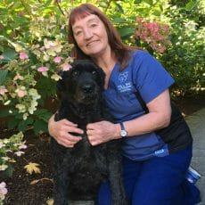 Bonnie Tolley from Mill Bay Veterinary Hospital kneeling beside a black dog