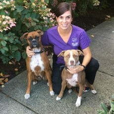 Brittany Myhre from Mill Bay Veterinary Hospital kneeling besides two dogs