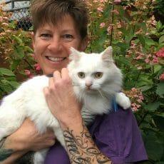 Nina Sleik from Mill Bay Veterinary Hospital holding a white, fluffy cat
