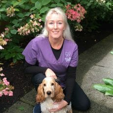 Ineke van Biezen from Mill Bay Veterinary Hospital kneeling beside a golden dog