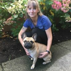 Tammie Martin from Mill Bay Veterinary Hospital kneeling beside a french bulldog