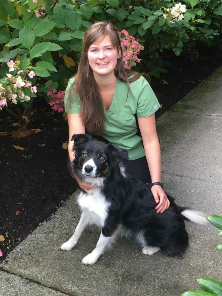 Tara Truswell from Mill Bay Veterinary Hospital kneeling beside a border collie dog